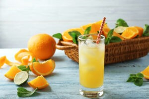 Glass with delicious orange juice and straw on wooden table